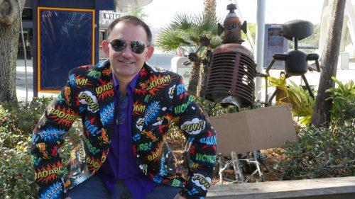 Josh Pies in loud coat, smiling